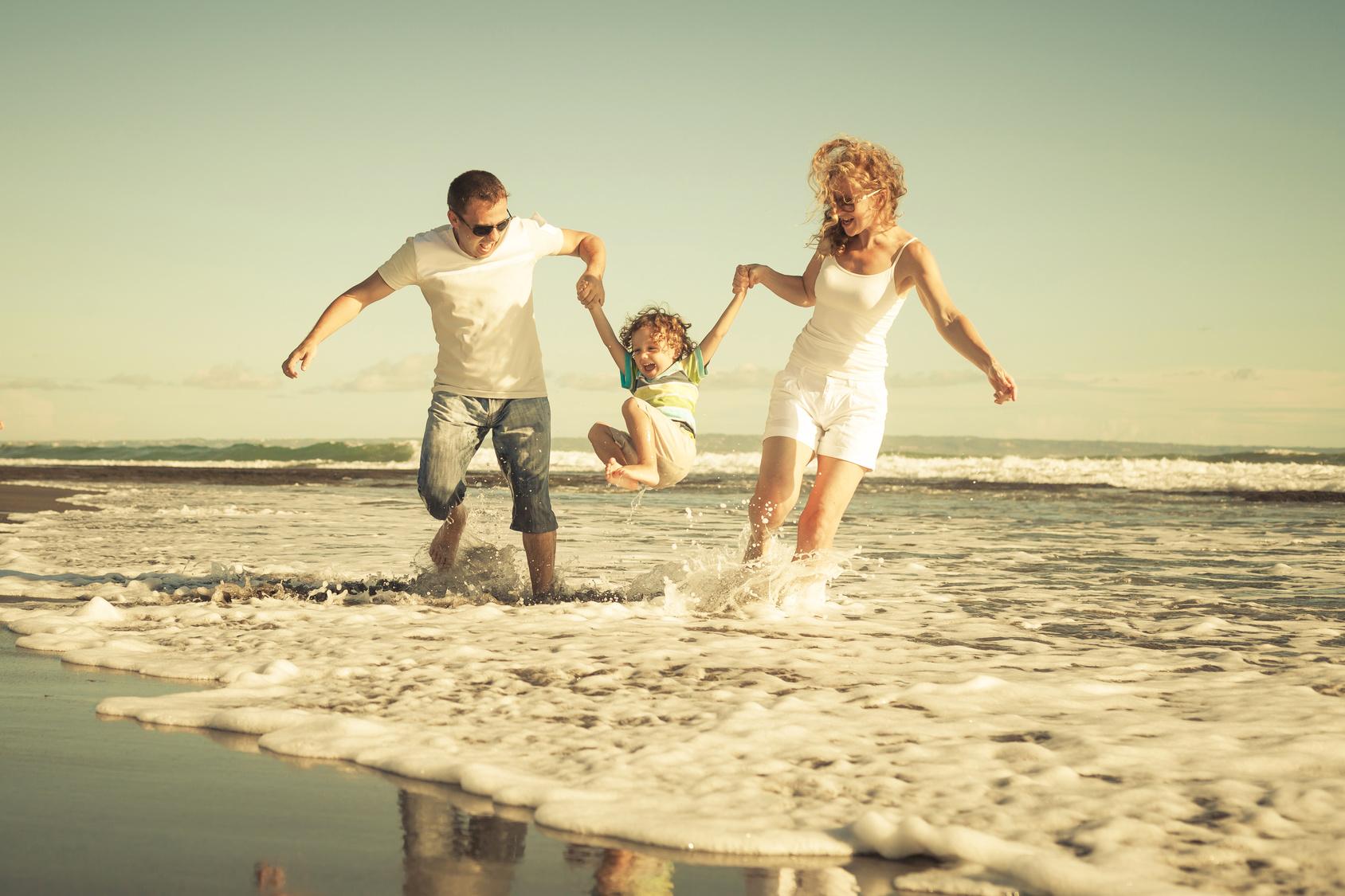 Szczęśliwa rodzina grająca na plaży